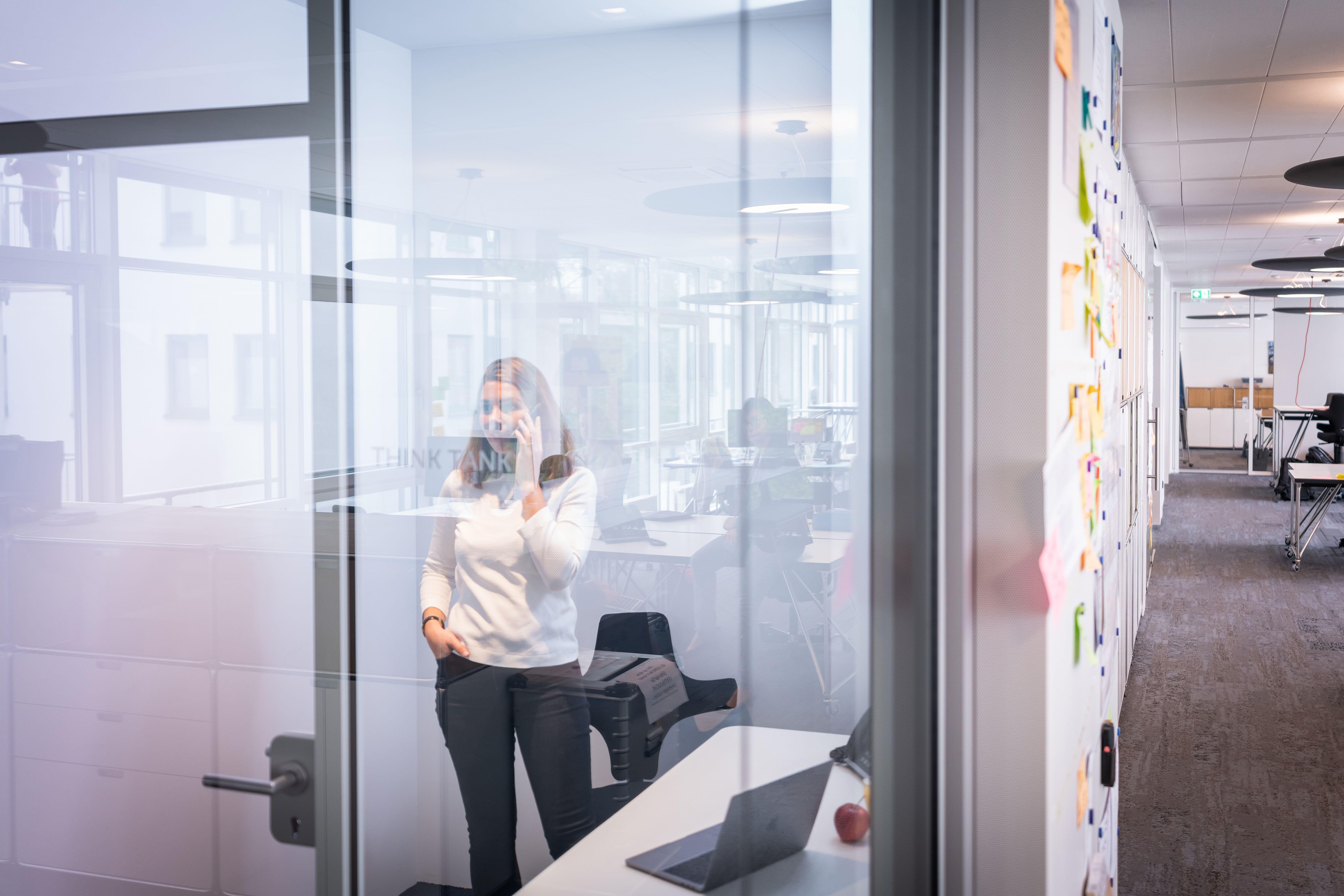 Person telefoniert in einem Raum mit Glasfront