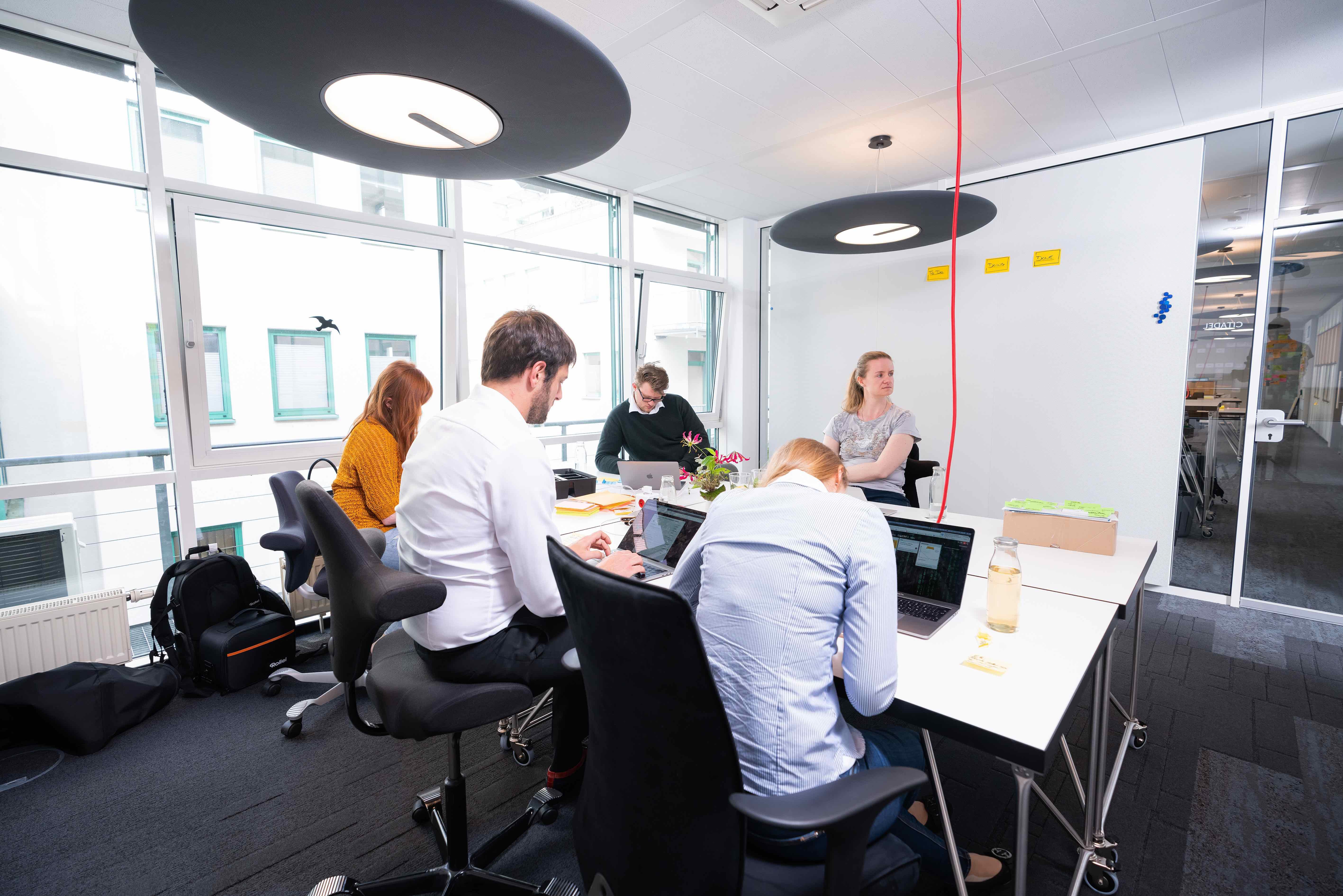 Menschen arbeiten in einem Raum um einen großen Tisch herum, Wände mit Schallschutzelementen, Lampen mit Schallschutzelementen, Teppich