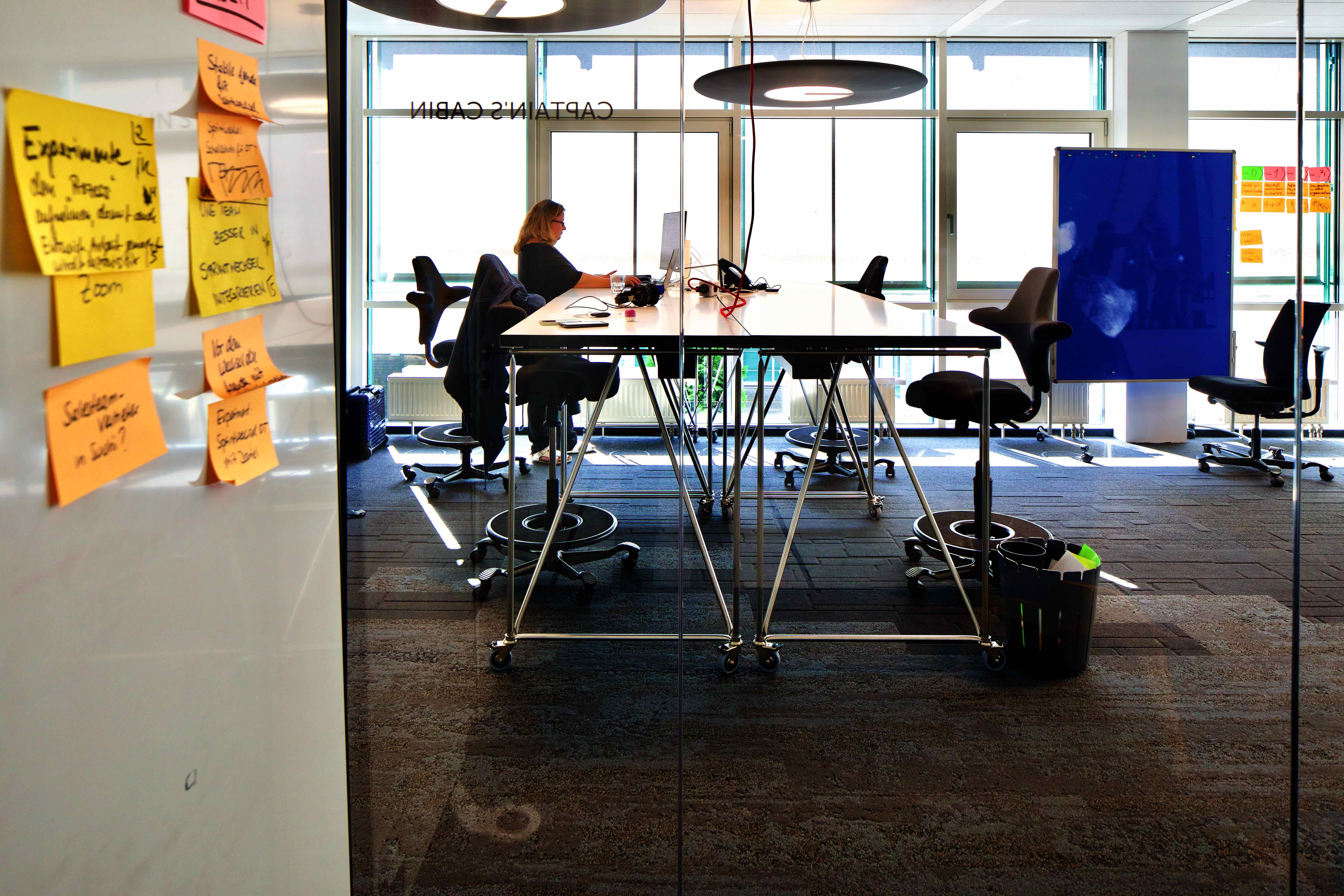 Blick in ein Großraumbüro mit hohen Tischen auf Rollen, Stühlen auf Rollen, und anderem Arbeitsmaterial auf Rollen