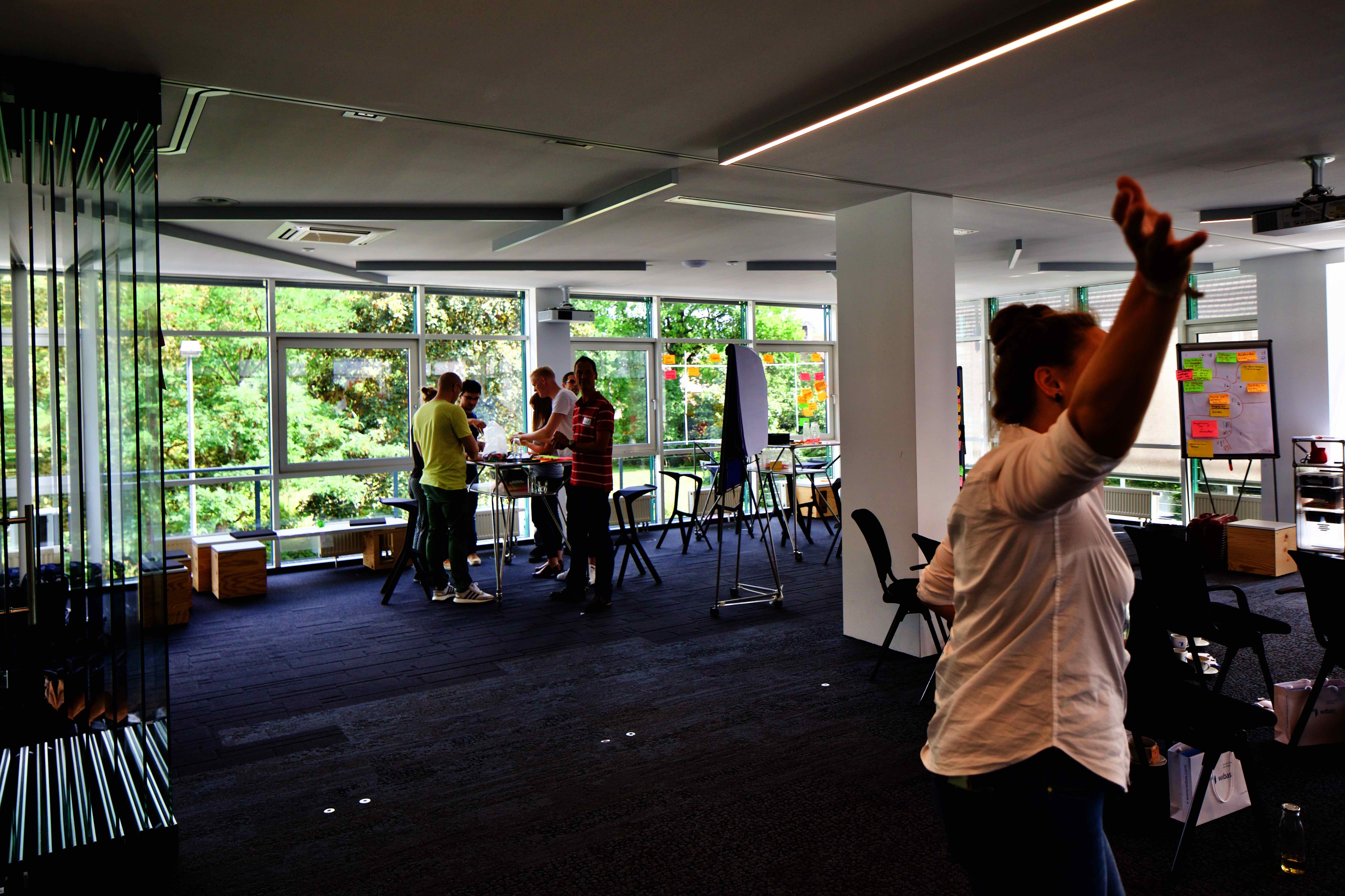 großer Raum mit Stühlen und Arbeitsbereich, in dem Menschen um hohe Tische stehen und zusammen arbeiten