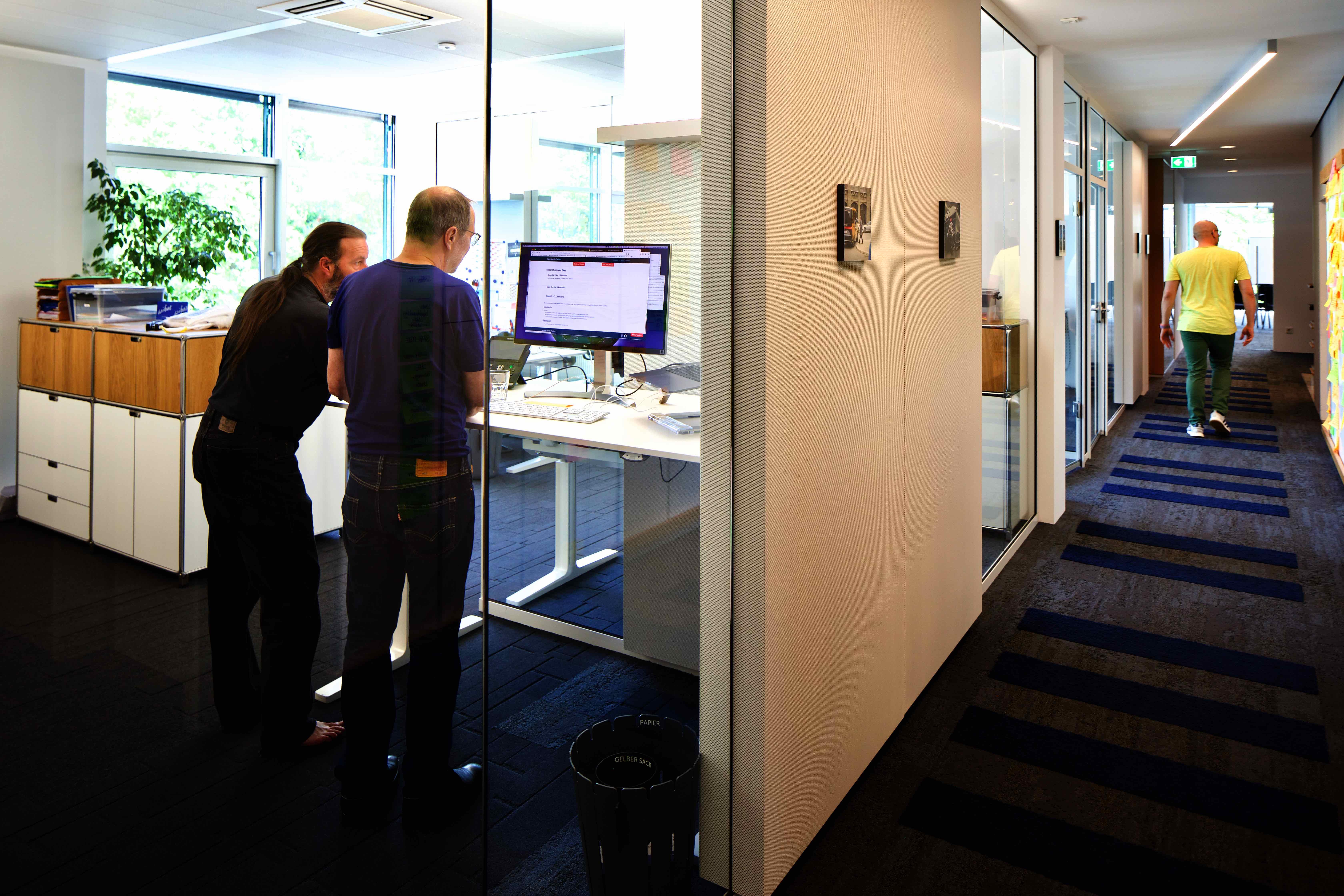 Büro links, rechts Flur, mit Glaswänden und Schallschutzelementen getrennt, mit arbeitenden Menschen