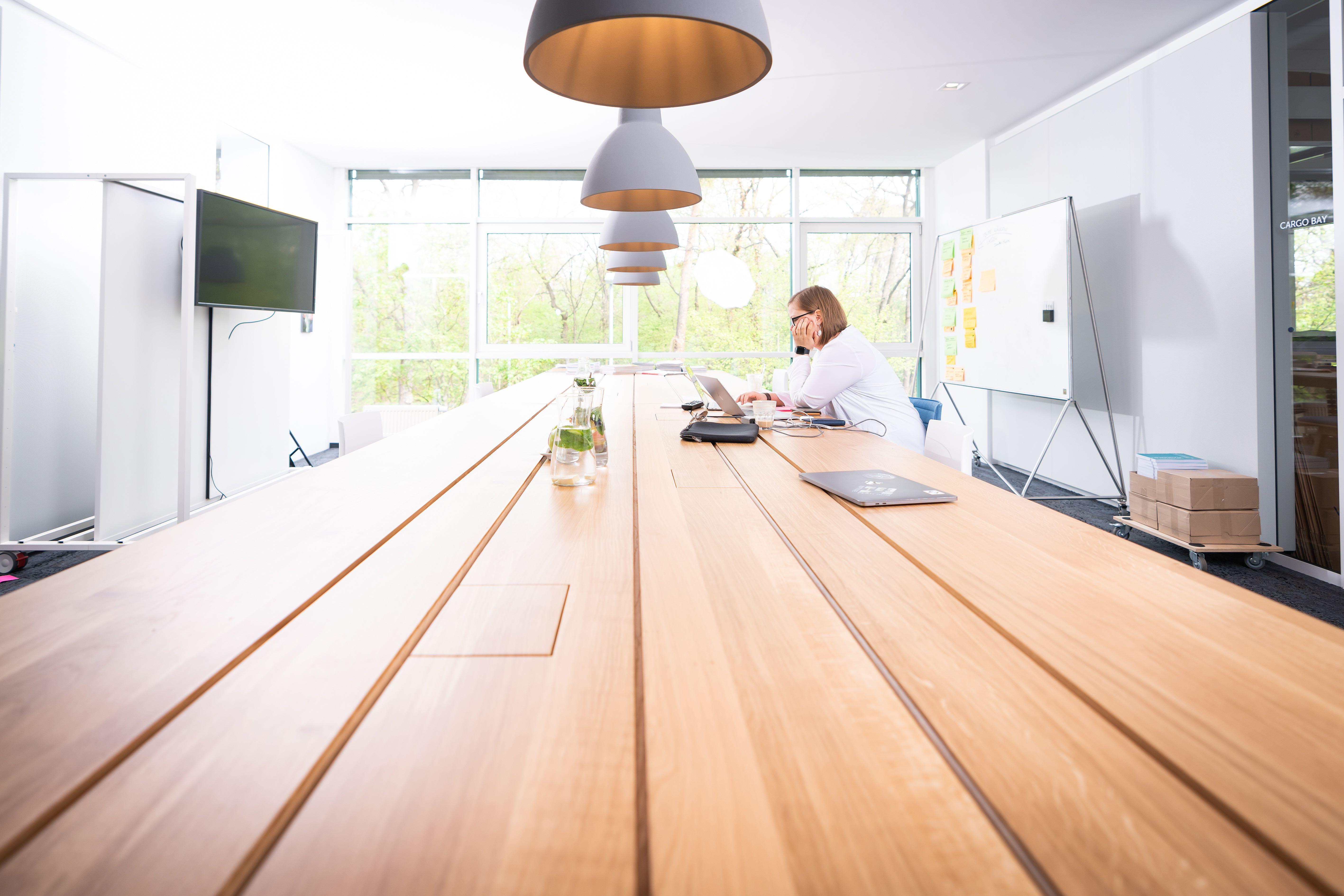 langer Holztisch mit einer Person, die daran arbeitet